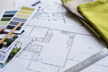 dessin: La table de designer d'intérieur de travail, un plan architectural de la maison, une palette de couleurs, du mobilier et des échantillons de tissu de couleur jaune et gris. Dessins et plans de décoration de la maison.