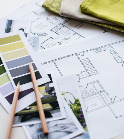 samples: Interior designers working table, an architectural plan of the house, a color palette, furniture and fabric samples in yellow and grey color. Drawings and plans for house decoration.