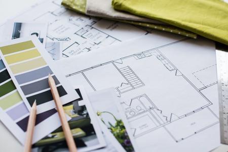 La table de designer d'intérieur de travail, un plan architectural de la maison, une palette de couleurs, du mobilier et des échantillons de tissu de couleur jaune et gris. Dessins et plans de décoration de la maison. Banque d'images