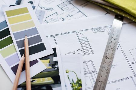 Arbeitstisch Innenarchitekt, ein Architekturplan des Hauses, eine Farbpalette, Möbel und Stoffmuster in gelb und grau dargestellt. Zeichnungen und Plänen für Hausdekoration.
