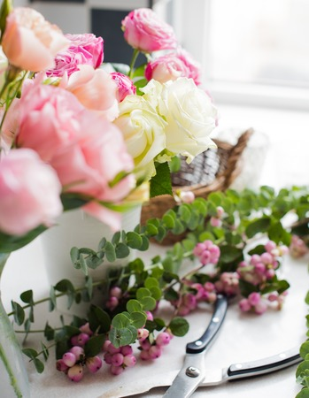 arranging: Fresh flowers, leaves, and tools to create a bouquet on a table, florists workplace.