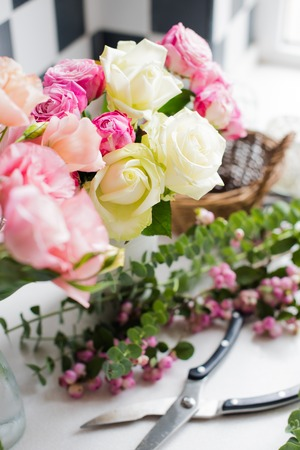 Fresh flowers, leaves, and tools to create a bouquet on a table, florist's workplace.