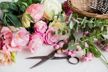 složení: Čerstvé květiny, listy, a nástroje k vytvoření kytici na pracovišti stolu a květinářství.