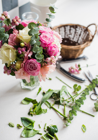 floristry: Just created bouquet of fresh flowers and leaves, scissors on a table, florists studio.