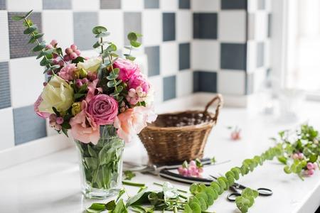 arreglo floral: Sólo creado ramo de flores frescas y hojas, tijeras en una mesa, el taller de floristería.