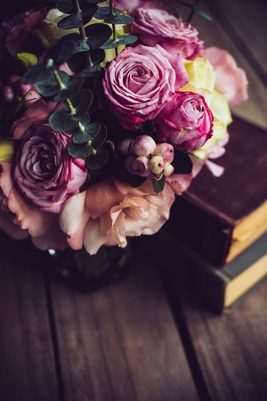 arrangements: Elegant bouquet of pink flowers and ancient books on an old wooden board with copy space. Vintage decor.