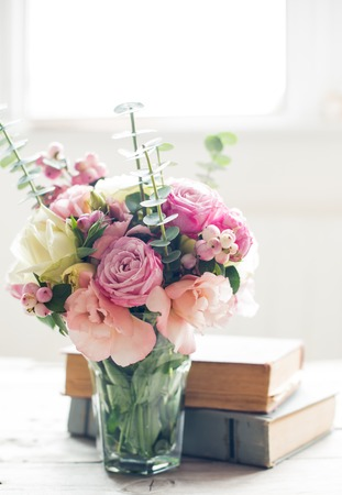 Elegant bouquet of pink flowers and ancient books on a tabke with backlight. Vintage decor. Foto de archivo