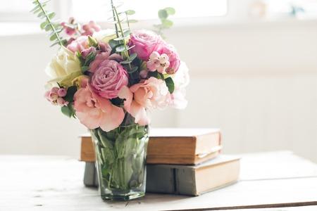 백라이트와 tabke에 핑크 꽃과 고대의 책의 우아한 꽃다발. 빈티지 장식.