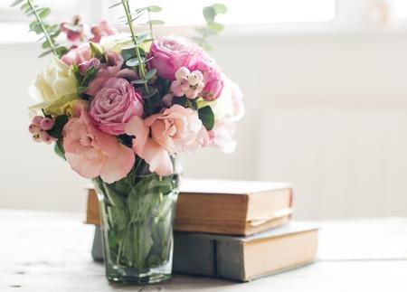 Eleganter Blumenstrauß der rosafarbenen Blumen und alte Bücher auf einem Tabke mit Hintergrundbeleuchtung. Weinlese-Dekor.