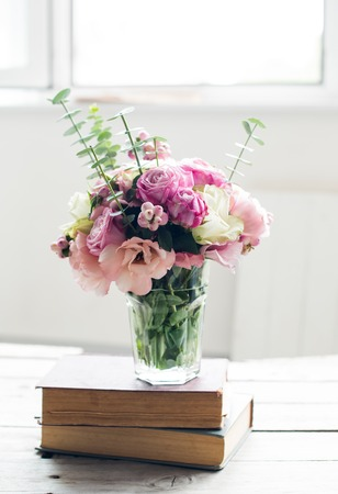 arrangements: Elegant bouquet of pink flowers and ancient books on a tabke with backlight. Vintage decor. Stock Photo