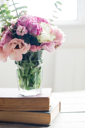 ancient books: Elegant bouquet of pink flowers and ancient books on a tabke with backlight. Vintage decor. Stock Photo