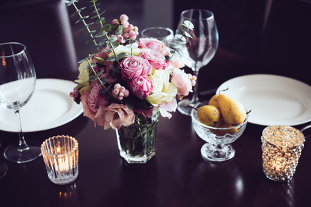 night table: Bouquet of pink flowers on a table set for dinner with candles, close-up