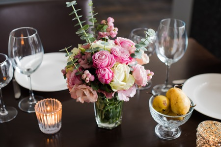 table set: Bouquet of pink flowers on a table set for dinner with candles, close-up