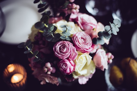 arrangements: Bouquet of pink flowers on a table set for dinner with candles, close-up