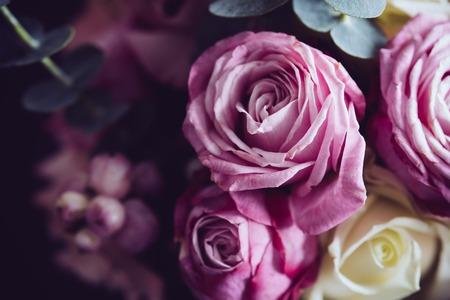 Elegant boeket van roze en witte rozen op een donkere achtergrond, zachte nadruk, close-up. Romantische hipster achtergrond. Vintage filter.