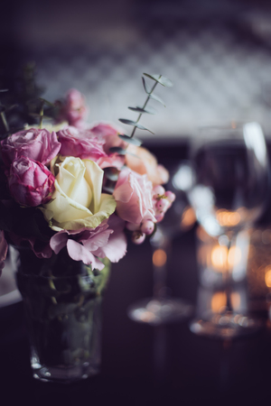 table setting: Bouquet of pink flowers on a table set for dinner with candles, close-up