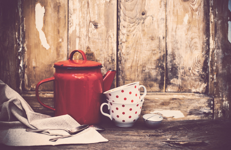 house with style: Vintage kitchen decor, red enamel coffee pot and cups with polka dots on an old wooden board background with copy space. Rustic home decor.