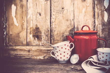 room wall: Vintage kitchen decor, red enamel coffee pot and cups with polka dots on an old wooden board background with copy space. Rustic home decor.