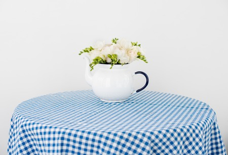 Lovely fresh bouquet of white summer roses and freesias in vintage enamel tea pot on a table with blue checkered woven fabric tablecloth. Retro style interior decoration with copy space. Stock Photo