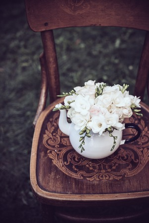 rosas blancas: fiesta de la boda del verano decoración festiva, precioso ramo fresco de rosas blancas y fresias verano en la olla de té del esmalte de la vendimia en una vieja silla de madera de color marrón. decoración al aire libre de estilo retro, fondo de la hierba.