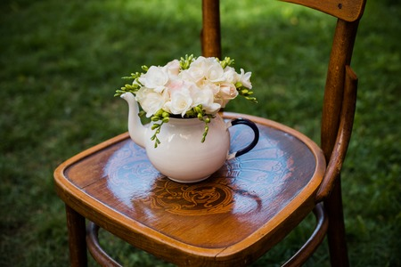 silla de madera: fiesta de la boda del verano decoración festiva, precioso ramo fresco de rosas blancas y fresias verano en la olla de té del esmalte de la vendimia en una vieja silla de madera de color marrón. decoración al aire libre de estilo retro, fondo de la hierba.