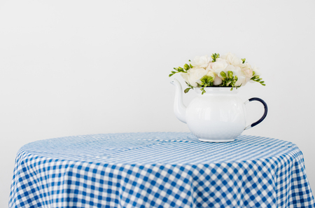 Lovely fresh bouquet of white summer roses and freesias in vintage enamel tea pot on a table with blue vichy tablecloth. Retro style interior decoration with copy space.