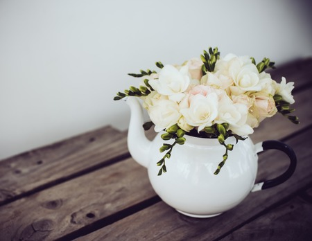 flower arrangement: Lovely fresh bouquet of white summer roses and freesias in vintage enamel tea pot on an old brown wooden board. Retro style interior decoration with copy space.