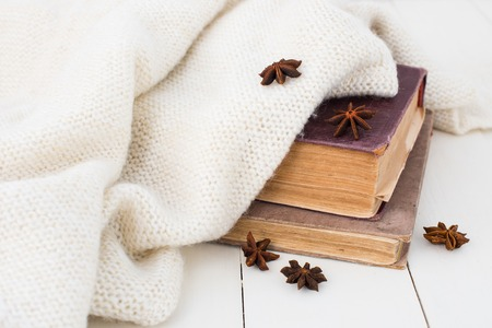estrella de la vida: Winter still-life, old vintage books and knitted sweater on white painted wooden background.