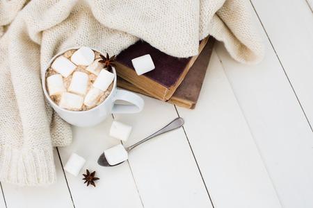 Gezellige winter home achtergrond, kopje warme cacao met heemst, oude vintage boeken en warme gebreide trui op wit geschilderde houten plank achtergrond.