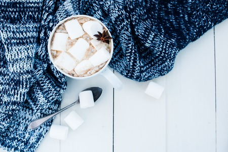 Cozy winter home background, cup of hot cocoa with marshmallow, old vintage books and warm knitted sweater on white painted wooden board background. Stock Photo