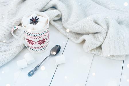 居心地の良い冬の家庭背景、マシュマロ、スターアニス、古いビンテージ本ホワイト塗装済み木製ボードの背景に暖かいニットのセーターとホット