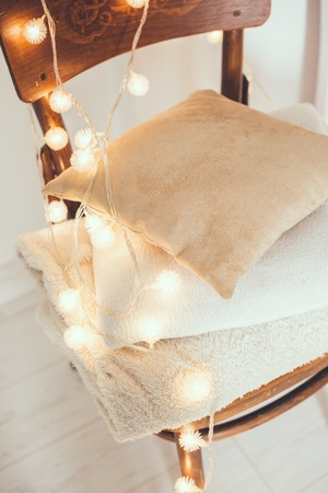 warm home: A stack of white and beige pillows and blankets with string lights on vintage wooden chair. Cozy interior details, soft and warm home decor.