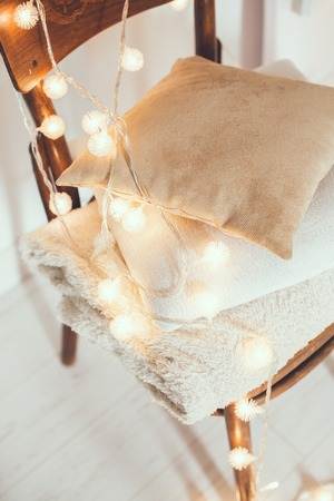 string lights: A stack of white and beige pillows and blankets with string lights on vintage wooden chair. Cozy interior details, soft and warm home decor.