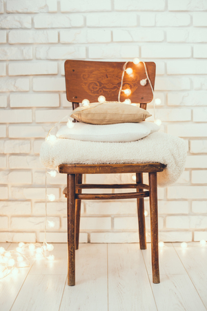 homelike: A stack of white and beige pillows and blankets with string lights on vintage wooden chair. Cozy interior details, soft and warm home decor.