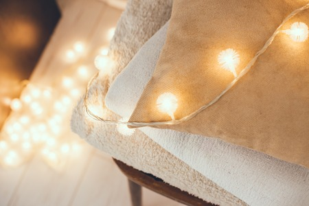 quiet: A stack of white and beige pillows and blankets with string lights on vintage wooden chair. Cozy interior details, soft and warm home decor.