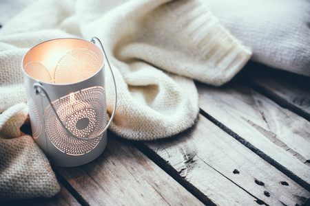 Przytulne i miękkie tło zima, sweter z dzianiny i świec na starym rocznika desce. Święta Bożego Narodzenia w domu.