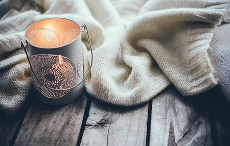 homelike: Cosy and soft winter background, knitted sweater and candles on an old vintage wooden board. Christmas holidays at home.