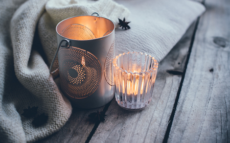 Gezellig en zachte winter achtergrond, gebreide trui en kaarsen op een oude vintage houten plank. Kerstvakantie thuis.