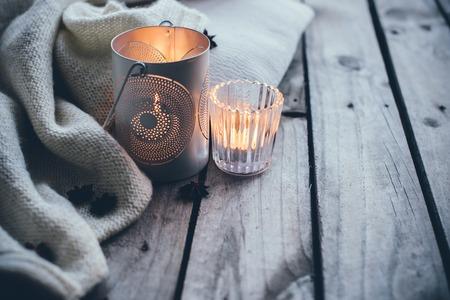 Sfondo accogliente e morbido inverno, maglione lavorato a maglia e candele su una vecchia tavola di legno d'epoca. Vacanze di Natale a casa.