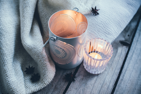 quiet: Cosy and soft winter background, knitted sweater and candles on an old vintage wooden board. Christmas holidays at home.