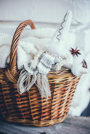 homelike: Soft white knitted sweater and handmade doll in a wicker basket on an old wooden board. Christmas holiday decor.