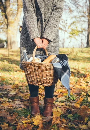 picnic blanket: A young woman holding a basket with a blanket, baguette and coffee, close-up. Autumn picnic in the park.