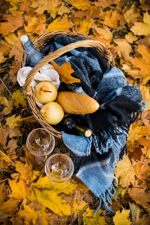 autumn food: Basket with a blanket, coffee, food, wine and glasses on yellow autumn leaves. A cozy autumn picnic in the park, a warm autumn day.