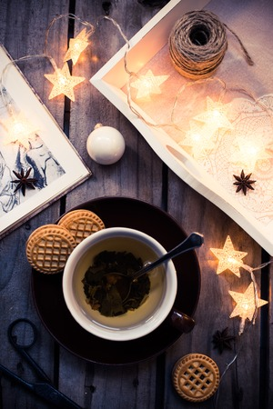 vintage objects: Winter holiday background: cup of tea, Christmas lights and other home decoration on vintage wooden table. Cozy holidays at home. Stock Photo