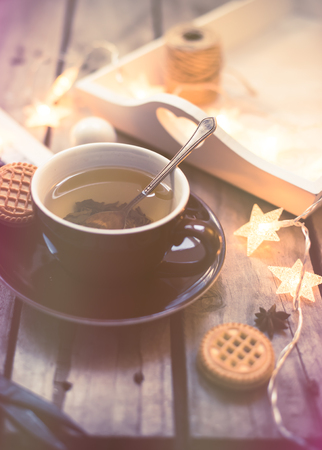 christmas tea: Winter holiday background: cup of tea, Christmas lights and other home decoration on vintage wooden table. Cozy holidays at home. Stock Photo