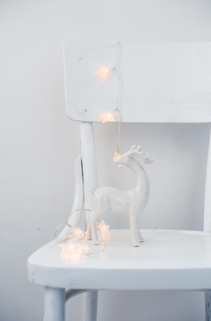 christmas decor: Christmas lights and ceramic deer on vintage white painted chair, holiday interior decor