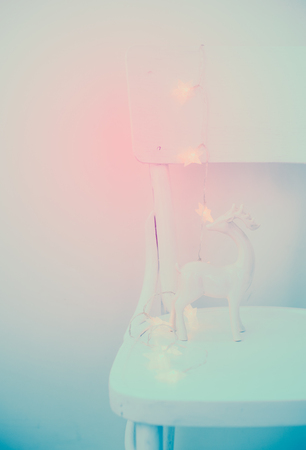 soft colors: Christmas lights and ceramic deer on vintage white painted chair, lovely holiday bachground in soft colors Stock Photo