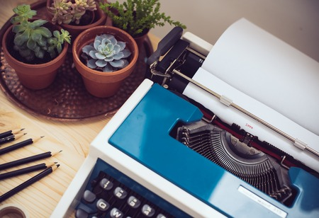 work from home: Stylish hipster work space, retro typewriter and green plants on office desk. Writers home office.