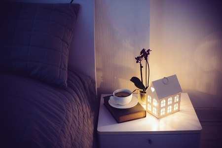Cozy evening bedroom interior, cup of tea and a night light on the bedside table. Home interior decor with warm light. Stock fotó - 51446479