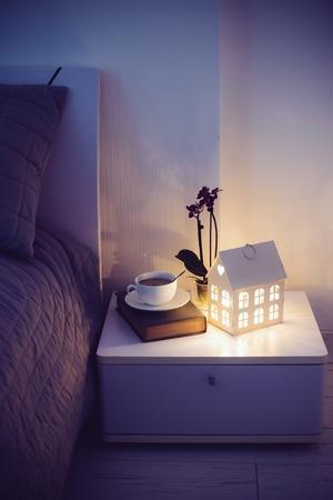 Gezellige avond slaapkamer interieur, een kop thee en een 's nachts licht op het nachtkastje. Huis interieur met warm licht. Stockfoto